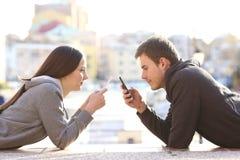 Par av tonår som hemsökas med smarta telefoner arkivfoto