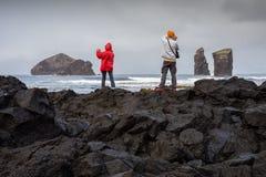 Par av turister som fotograferar Mosteiros den vulkaniska stranden Royaltyfri Foto
