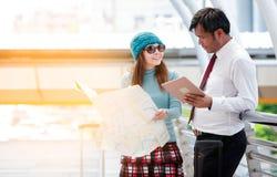Par av turister som konsulterar en stad, vägleder sökande av lägen Arkivfoto