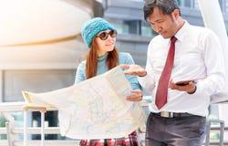 Par av turister som konsulterar en stad, vägleder sökande av lägen Arkivbild