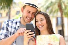 Par av turister som kontrollerar destinationen på telefonen royaltyfria foton