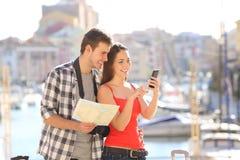 Par av turister som kontrollerar online-information på semester royaltyfri foto