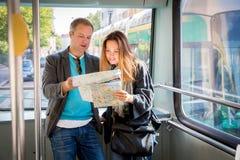 Par av turister som läser stadsöversikten som rider spårvagnen Royaltyfri Bild
