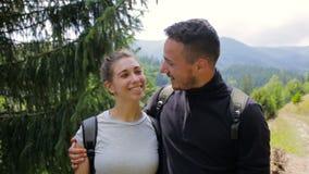 Par av turister som poserar och ser kameran mot bakgrunden av bergen lager videofilmer