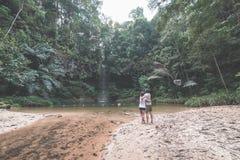 Par av turister som ser en bedöva mångfärgad naturlig pöl och vattenfall i rainforesten av den Lambir kullenationalparken, Royaltyfria Bilder