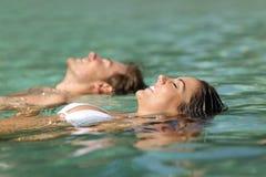 Par av turister som simmar i havet av en tropisk semesterort Arkivbilder