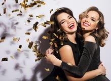 Par av två Rich Women Laughing med kristallen av Champagne lyx mått för 1 mjölkar 3 5 6 8 några för coctailkokosnötcolada för kub royaltyfri fotografi