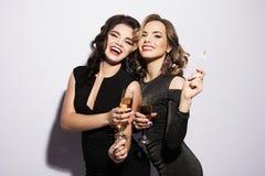 Par av två Rich Women Laughing med kristallen av Champagne lyx mått för 1 mjölkar 3 5 6 8 några för coctailkokosnötcolada för kub royaltyfri bild