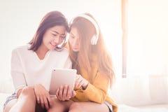 Par av unga asiatiska kvinnor som använder minnestavlan på vit säng med happi royaltyfri bild