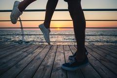 Par av unga hipstervänner som kysser som är nära upp på ben och gymnastikskor på stranden på soluppgånghimmel på trädäcksommartid royaltyfri foto