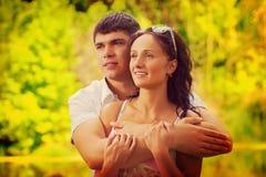 Par av unga män och kvinnan som kramar och ser det distan Arkivbild
