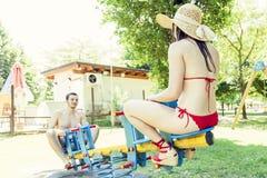 Par av unga vuxna människor har gyckel på en gungbräde Arkivfoto