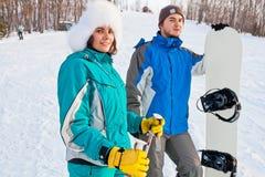 Par av unga vuxna människor på en skidasemesterort Arkivfoton