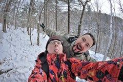 Par av ungdomarsom har gyckel i vinterskog Royaltyfria Bilder