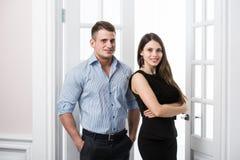 Par av ungt stilfullt affärsfolk i kontoret för dörröppningshemmiljövind Royaltyfria Foton