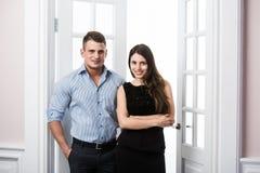 Par av ungt stilfullt affärsfolk i kontoret för dörröppningshemmiljövind Royaltyfria Bilder