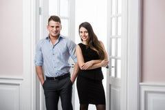 Par av ungt stilfullt affärsfolk i kontoret för dörröppningshemmiljövind Royaltyfri Foto
