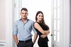Par av ungt stilfullt affärsfolk i kontoret för dörröppningshemmiljövind Arkivfoto