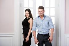 Par av ungt stilfullt folk i det stående kontoret för dörröppningshemmiljövind tillbaka till varandra Royaltyfria Foton