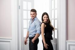 Par av ungt stilfullt folk i det stående kontoret för dörröppningshemmiljövind tillbaka till varandra Royaltyfri Bild