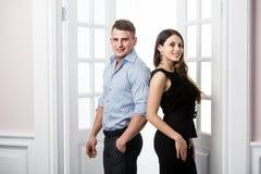 Par av ungt stilfullt folk i det stående kontoret för dörröppningshemmiljövind tillbaka till varandra Arkivfoton