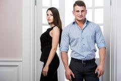 Par av ungt stilfullt folk i det stående kontoret för dörröppningshemmiljövind tillbaka till varandra Royaltyfri Foto