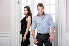 Par av ungt stilfullt folk i det stående kontoret för dörröppningshemmiljövind tillbaka till varandra Royaltyfri Fotografi