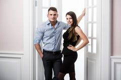 Par av ungt stilfullt folk i kontoret för dörröppningshemmiljövind Fotografering för Bildbyråer