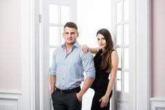 Par av ungt stilfullt folk i kontoret för dörröppningshemmiljövind Arkivfoto