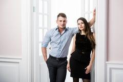 Par av ungt stilfullt folk i kontoret för dörröppningshemmiljövind Royaltyfria Bilder