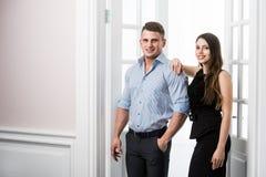 Par av ungt stilfullt folk i kontoret för dörröppningshemmiljövind Royaltyfri Bild