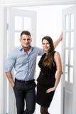 Par av ungt stilfullt folk i kontoret för dörröppningshemmiljövind Arkivbilder