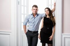 Par av ungt stilfullt folk i kontoret för dörröppningshemmiljövind Royaltyfri Fotografi