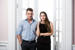 Par av ungt stilfullt folk i kontoret för dörröppningshemmiljövind Arkivfoton