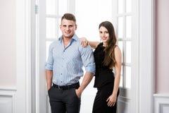 Par av ungt stilfullt folk i kontoret för dörröppningshemmiljövind Flickan satte hennes hand till hans skuldra Royaltyfri Bild