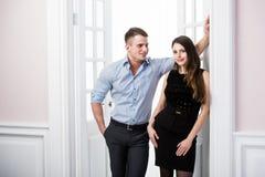 Par av ungt stilfullt folk i kontoret för dörröppningshemmiljövind som till varandra ser Arkivfoton