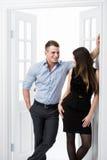 Par av ungt stilfullt folk i kontoret för dörröppningshemmiljövind som till varandra ser Royaltyfri Bild