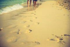 Par av vänner som går på varje på soluppgång - foten skrivar ut stranden Arkivfoton