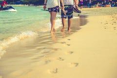 Par av vänner som går på varje på soluppgång - foten skrivar ut stranden Fotografering för Bildbyråer