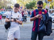 Par av vänner som stöttar Real Madrid, och Barcelona som håller ögonen på deras Smartphones på Santiago Bernabeu Stadium Gates fö Arkivfoto
