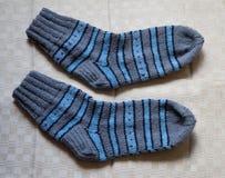 Par av varma woolen färgrika stack sockor på en linnebakgrund Arkivbild