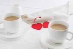 Par białe filiżanki kawy na białym drewnianym tle Obraz Stock