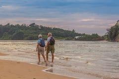 Par casado de personas mayores en la playa en la orilla del océano fotos de archivo