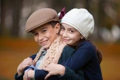 Par de los niños que sonríen y que llevan un casquillo cada uno imagen de archivo