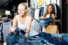 Par de tejanos que hace compras de las muchachas junto Foto de archivo