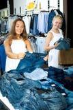 Par de tejanos que hace compras de las muchachas junto Imagen de archivo libre de regalías