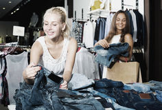 Par de tejanos que hace compras de las muchachas junto Foto de archivo libre de regalías