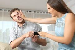 Par eller vänner som slåss för en mobiltelefon Royaltyfri Foto