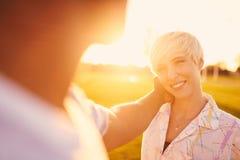 Par för blandat lopp av millennial i ett gräsfält som ser ine ögon under sommarsemester arkivbild