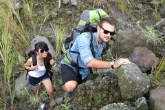 Par för blandat lopp går trekking tillsammans och att gå på ett stigande Royaltyfri Foto